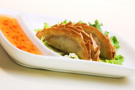 Crisp pork and chicken dumplings served on a bed of lettuce and sweet & sour sauce. photo