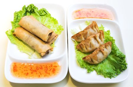 Plates of vegetable Spring rolls and crisp pork and chicken dumplings served on a bed of lettuce and sweet & sour sauce. photo