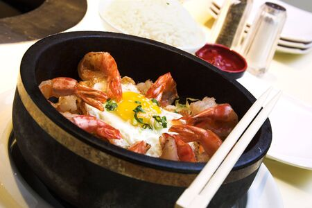 delicacy: Traditional Korean delicacy made with vegetables and shrimp, served with fried egg and garnished with sesame seeds and chopped green onions. Dish is served with steamed rice on the side. Stock Photo