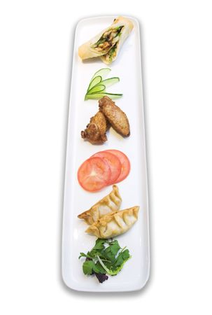 Beautifully laid out appetizer plate of vegetable spring roll, chicken wings and japanese dumpling. Served with tomatoes, cucumbers and  green salad.