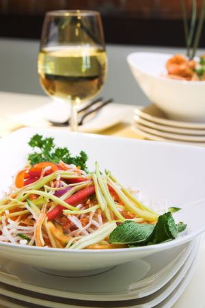 taro: Exotic salad made with vermicelli, green mango, cucumber, fried taro and green onions. Garnished with parsley and mint. Served with white wine. Stock Photo