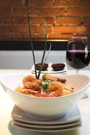 wine and food: Traditional Thai delicacy made from jumbo shrimps, Thai noodles and prepared with select spices. Garnished with finely chopped green onions. Served with red wine.