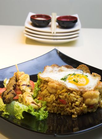 Exotic dish of Indonesian fried rice made with chicken and shrimp, topped with a fried egg. Chicken and beef satays are served on the side. Stock Photo - 385375