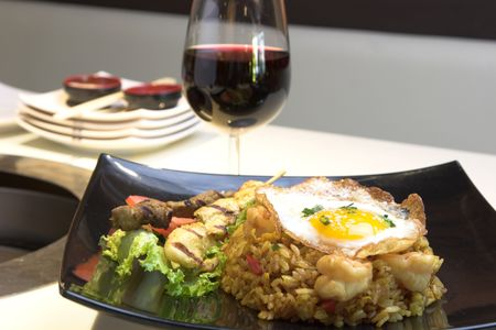 Exotic dish of Indonesian fried rice made with chicken and shrimp, topped with a fried egg. Chicken and beef satays are served on the side. Stock Photo - 385374