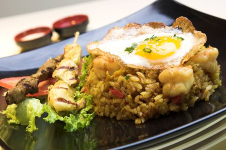 Exotic dish of Indonesian fried rice made with chicken and shrimp, topped with a fried egg. Chicken and beef satays are served on the side.