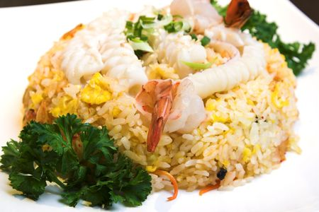 Delicious seafood fried rice with shrimp, crab eggs and a light garnishing of spring onions. Served with traditional sauces. Stock Photo