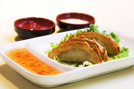 Crisp pork and chicken dumplings served on a bed of lettuce and sweet & sour sauce. Served with traditional sauces. photo