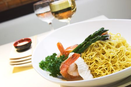 Delicious seafood fried noodles with shrimps, fish, squid and mushroom. Served with asparagus. Stock Photo - 385365