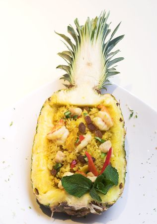 An exotic dish of fried rice inside a pineapple shell. The scattering of fine pieces around the dish is a part of the stylish of the dish. photo