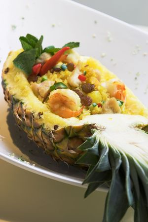 An exotic dish of seafood fried rice inside a pineapple shell. The scattering of fine pieces around the dish is a part of the stylish of the dish. photo