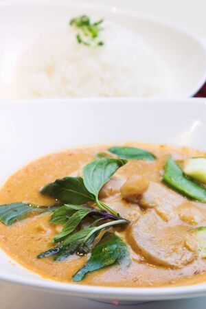 The famous Thai style red curry chicken served with steamed rice and garnished with basil leaves. Stock Photo