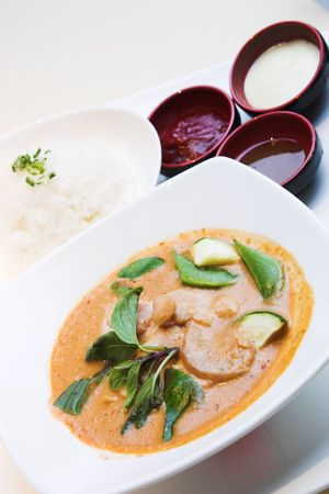 The famous Thai style red curry chicken served with steamed rice and garnished with basil leaves. Traditional sauces on the side. photo