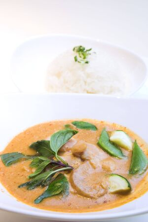 The famous Thai style red curry chicken served with steamed rice and garnished with basil leaves. photo