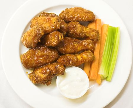 BBQ chicken wings served with celery sticks and carrots Stock Photo