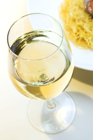 White wine served next to a plate of noodles Banco de Imagens
