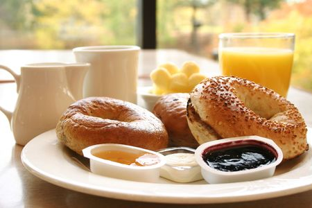 Classic breakfast of coffee, toasted bagels with butter and orange juice