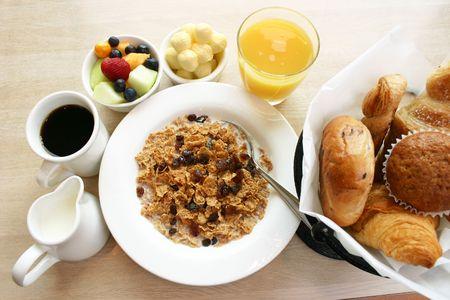 pasas: Desayuno saludable de los cereales, la fruta, muffins, bagels, y croissants. Servido con caf� y jugo de naranja.  Foto de archivo