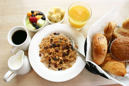 Healthy breakfast of cereal, fruit, muffins, bagels, and croissants. Served with coffee and orange juice.