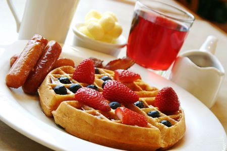 Blueberry waffles with maple syrup. Served with fresh strawberries and sausages on the side.