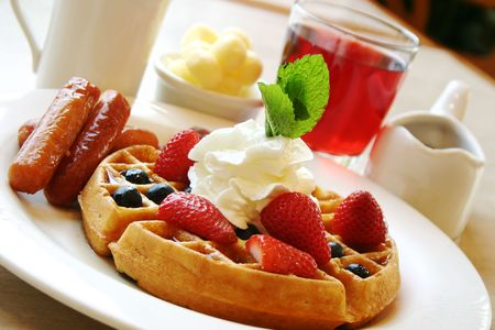 Blueberry waffles with maple syrup, topped with whipped cream and mint leaf. Served with fresh strawberries and sausages on the side. Stock Photo