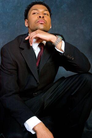 arrogancia: Un afro-americanas de negocios hombre se sienta con confianza  Foto de archivo