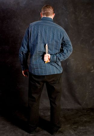 resentful: Man with a knife behind his back Stock Photo