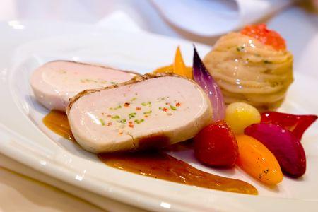 chutney: Filete del pavo de la corteza de la pacana relleno con el esp�rrago y las pimientas rojas, medley de los veh�culos de ra�z, patata del marquis y salsa picante del albaricoque. Foto de archivo