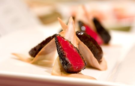 teepee: Poached beet root stuffed morel mushroom served along a tuille teepee.
