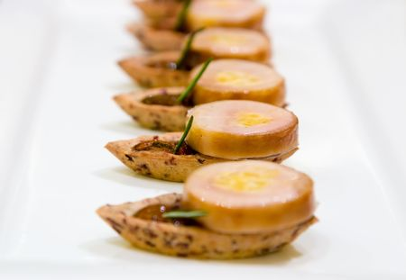 Torched foie gras and confit tian, layered with Manitoba wild rice and maple salad. Stock Photo