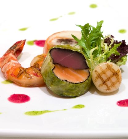 Tuna and fresh salmon wrapped in savoy cabbage. Served with grilled shrimps and scallops. Drizzled with pesto sauce and strawberry vinaigrette Stock Photo