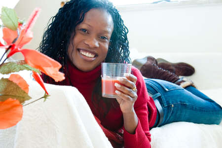 Portrait of a happy woman with a glass of tomato juice Imagens