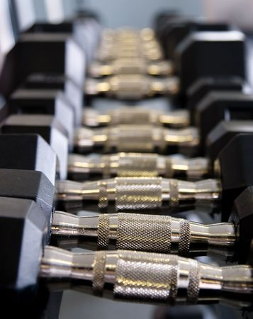 A full rack of dumbbells at a gym. Shallow DOF