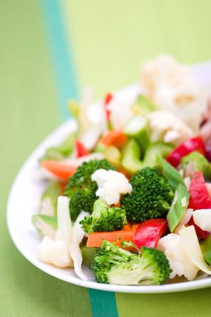 Vegetable salad greens made from broccoli, okra, cauliflower, red pepper lettuce and carrots. Shallow DOF.  Stock Photo