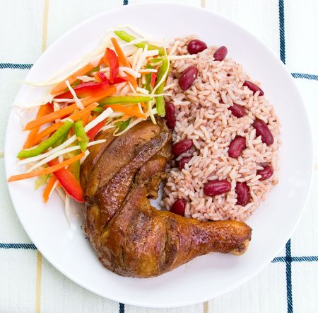 jamaican: Caribbean style jerk chicken served with rice mixed with red kidney beans. Dish accompanied with vegetable salad. Shallow DOF. Stock Photo
