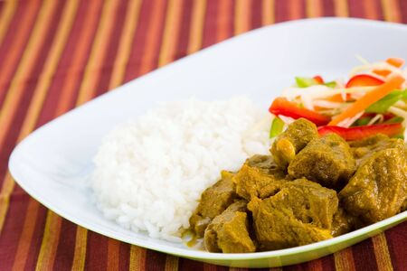 Caribbean style curried mutton served with steamed rice. Dish accompanied with vegetable salad. Shallow DOF.