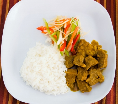 köri: Caribbean style curried goat served with steamed rice. Dish accompanied with vegetable salad. Shallow DOF.