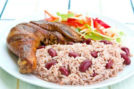 chuparse los dedos: El pollo del Caribe del tir�n del estilo sirvi� con el arroz mezclado con las habas de ri��n rojas. Plato acompa�ado con la ensalada vegetal. Dof bajo en el arroz.