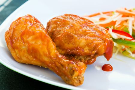 Fried chicken covered with tomato sauce - a caribbean speciality, served with grated vegetables. Shallow DOF.