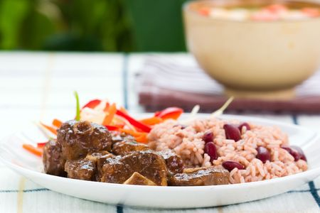 Caribbean style curried Oxtail served with rice mixed with red kidney beans. Dish accompanied with vegetable salad. Shallow DOF. Banco de Imagens