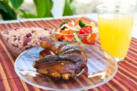 mouthwatering: Barbecued chicken leg also known as Jerk Chicken - Caribbean style served with vegetables, rice and lemonade.  Shallow DOF.