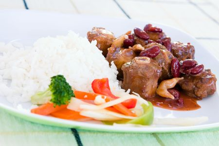 mouthwatering: Caribbean style curried Oxtail stew served with rice mixed with red kidney beans. Dish accompanied with vegetable salad. Shallow DOF. Stock Photo
