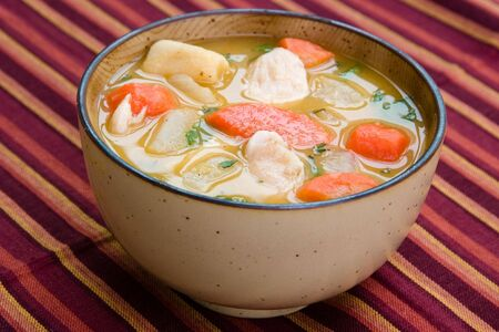 A bowl of caribbean style chicken soup with carrots, potatoes, herbs and cho-cho Stock Photo