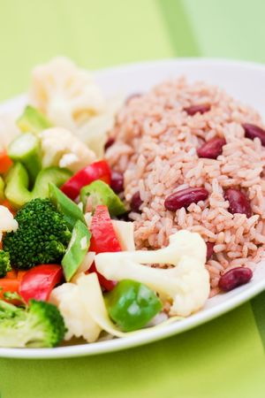 kidney beans: Caribbean style rice cooked with red kidney beans served with fresh garden vegetables. Shallow DOF.