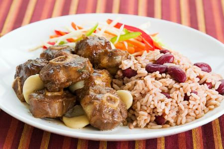 enticing: Caribbean style curried Oxtail served with rice mixed with red kidney beans. Dish accompanied with vegetable salad. Shallow DOF. Stock Photo