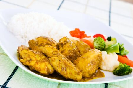 Curried chicken - Caribbean style served with rice and vegetables.  Shallow DOF.