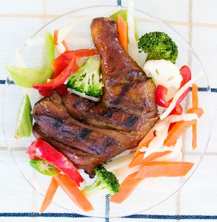 enticing: Barbecued chicken leg also known as Jerk Chicken - Caribbean style served with vegetables.  Shallow DOF.