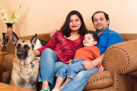 alsation: An East-Indian couple site in their living room with their son and dog Stock Photo