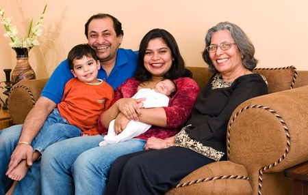 An East-Indian family sits in their living room Standard-Bild