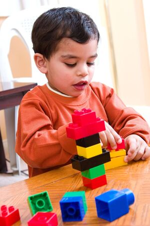 children  play: A child concentrated hard while playing with his blocks Stock Photo