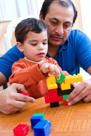 color block: A father plays with his son and helps him build with his blocks